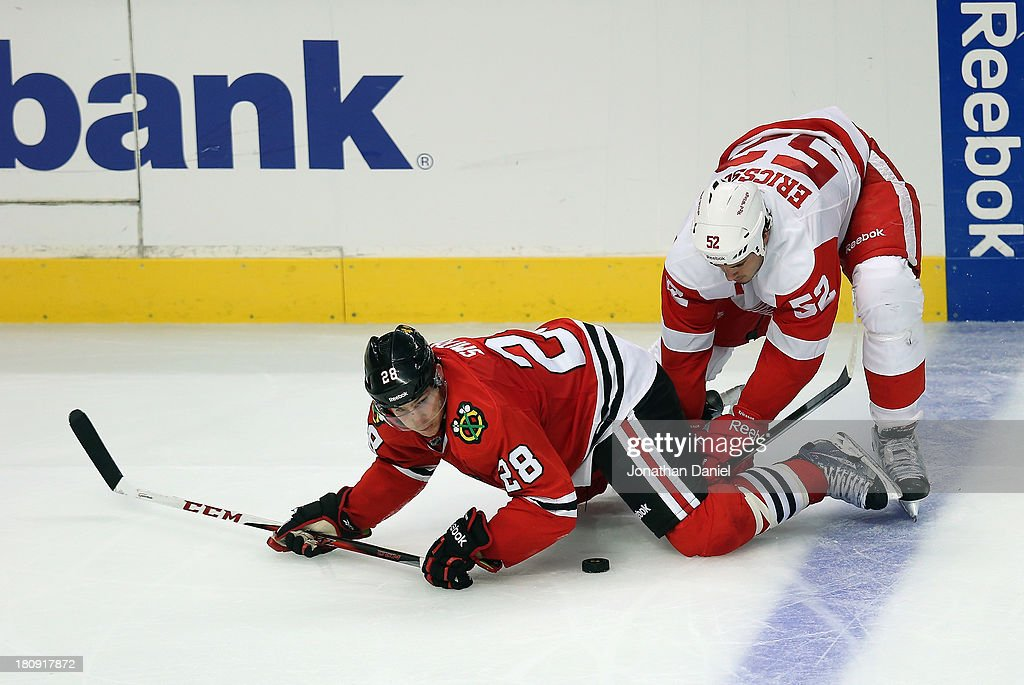 Ben Smith #28 of the Chicago Blackhawks is knocked down by <a gi-track='captionPersonalityLinkClicked' href=/galleries/search?phrase=Jonathan+Ericsson&family=editorial&specificpeople=2538498 ng-click='$event.stopPropagation()'>Jonathan Ericsson</a> #52 of the Detroit Red Wings during an exhibition game at United Center on September 17, 2013 in Chicago, Illinois. The Blackhawks defeated the Red Wings 2-0.