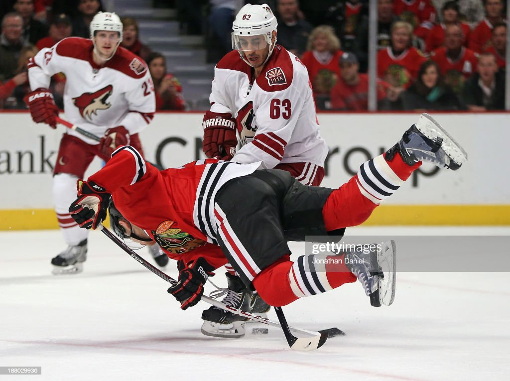 Ben Smith #28 of the Chicago Blackhawks is knocked to the ice by <a gi-track='captionPersonalityLinkClicked' href=/galleries/search?phrase=Mike+Ribeiro&family=editorial&specificpeople=203275 ng-click='$event.stopPropagation()'>Mike Ribeiro</a> #63 of the Phoenix Coyotes at the United Center on November 14, 2013 in Chicago, Illinois. The Blackhawks defeated the Coyotes 5-4 in a shootout.