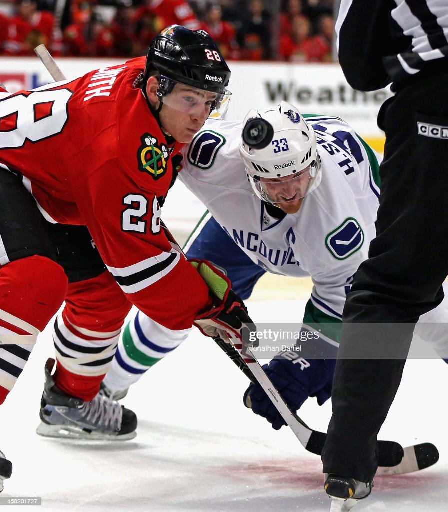 Ben Smith #28 of the Chicago Blackhawks keeps his eyes on the puck during a face-off with <a gi-track='captionPersonalityLinkClicked' href=/galleries/search?phrase=Henrik+Sedin&family=editorial&specificpeople=202574 ng-click='$event.stopPropagation()'>Henrik Sedin</a> #33 of the Vancouver Canucks at the United Center on December 20, 2013 in Chicago, Illinois.