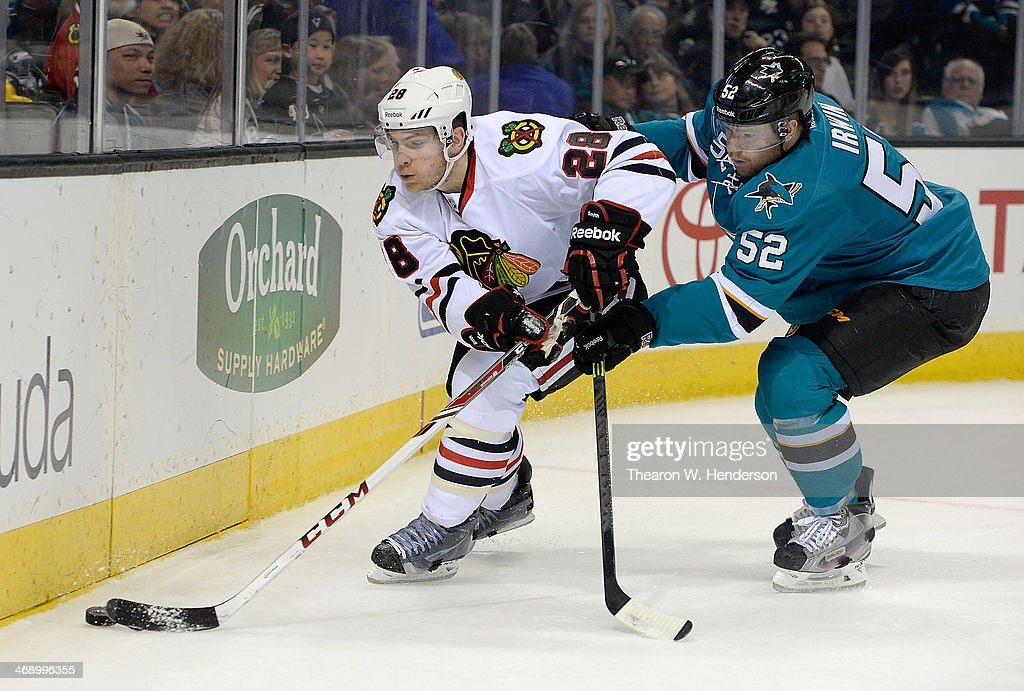 Ben Smith #28 of the Chicago Blackhawks skates behind the goal with control of the puck keeping it away from Matt Irwin #52 of the San Jose Sharks during the first period at SAP Center on February 1, 2014 in San Jose, California.