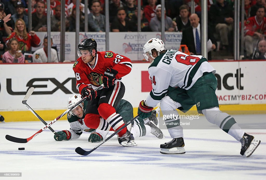 Ben Smith #28 of the Chicago Blackhawks skates between <a gi-track='captionPersonalityLinkClicked' href=/galleries/search?phrase=Jonas+Brodin&family=editorial&specificpeople=7832272 ng-click='$event.stopPropagation()'>Jonas Brodin</a> #25 (L) and <a gi-track='captionPersonalityLinkClicked' href=/galleries/search?phrase=Mikael+Granlund&family=editorial&specificpeople=5649678 ng-click='$event.stopPropagation()'>Mikael Granlund</a> #64 of the Minnesota Wild in Game Two of the Second Round of the 2014 NHL Stanley Cup Playoffs at the United Center on May 4, 2014 in Chicago, Illinois. The Blackhawks defeated the Wild 4-1.