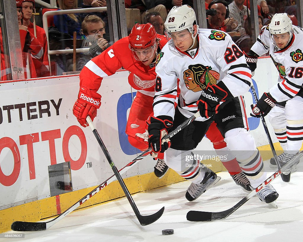 Ben Smith #28 of the Chicago Blackhawks skates free with the puck as Brendan Smith #2 of the Detroit Red Wings gives chase during an NHL game on January 22, 2014 at Joe Louis Arena in Detroit, Michigan.