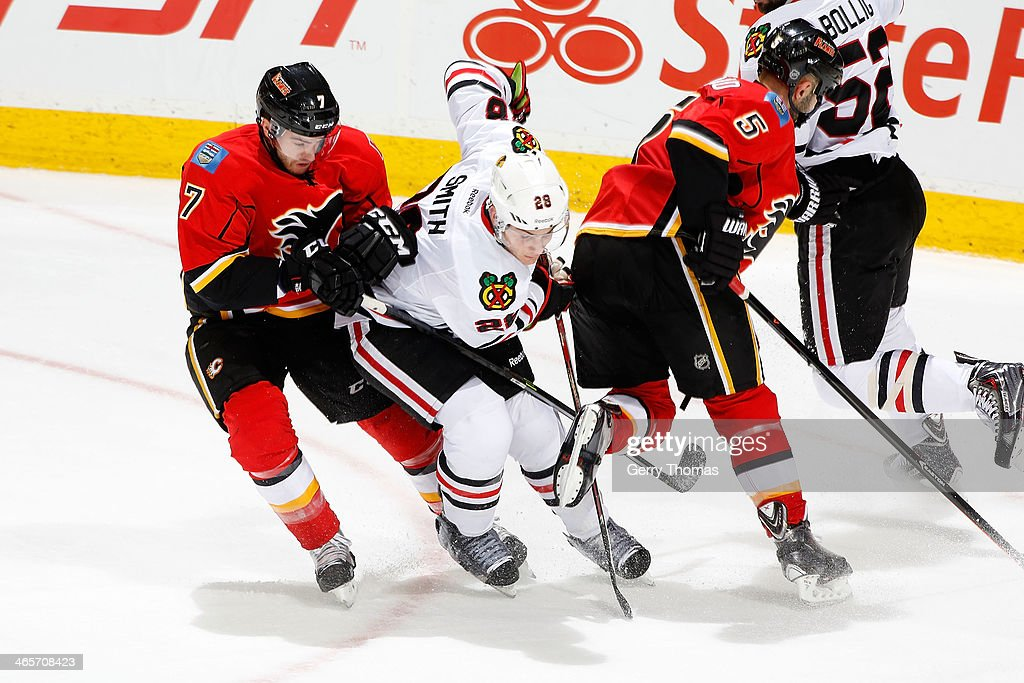 Ben Smith #28 of the Chicago Blackhawks skates in between <a gi-track='captionPersonalityLinkClicked' href=/galleries/search?phrase=TJ+Brodie&family=editorial&specificpeople=7220398 ng-click='$event.stopPropagation()'>TJ Brodie</a> #7 and <a gi-track='captionPersonalityLinkClicked' href=/galleries/search?phrase=Mark+Giordano&family=editorial&specificpeople=696867 ng-click='$event.stopPropagation()'>Mark Giordano</a> #5 of the Calgary Flames at Scotiabank Saddledome on January 28, 2014 in Calgary, Alberta, Canada.