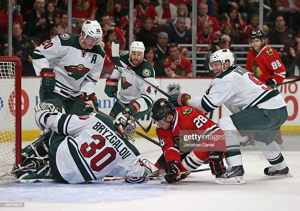 Ben Smith #28 of the Chicago Blackhawks tries to dig the puck out from under <a gi-track='captionPersonalityLinkClicked' href=/galleries/search?phrase=Ilya+Bryzgalov&family=editorial&specificpeople=2285430 ng-click='$event.stopPropagation()'>Ilya Bryzgalov</a> #30 of the Minnesota Wild as <a gi-track='captionPersonalityLinkClicked' href=/galleries/search?phrase=Ryan+Suter&family=editorial&specificpeople=583306 ng-click='$event.stopPropagation()'>Ryan Suter</a> #20 and <a gi-track='captionPersonalityLinkClicked' href=/galleries/search?phrase=Mikko+Koivu&family=editorial&specificpeople=584987 ng-click='$event.stopPropagation()'>Mikko Koivu</a> #9 defend in Game Two of the Second Round of the 2014 NHL Stanley Cup Playoffs at the United Center on May 4, 2014 in Chicago, Illinois. The Blackhawks defeated the Wild 4-1.