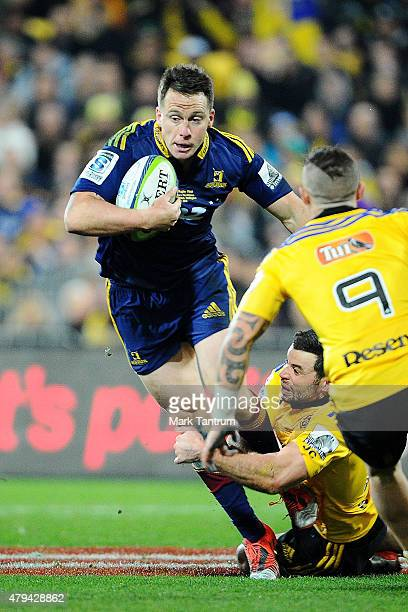 Ben Smith of the Highlanders breaks a tackle from Nehe MilnerSkudder of the Hurricanes during the Super Rugby Final match between the Hurricanes and...