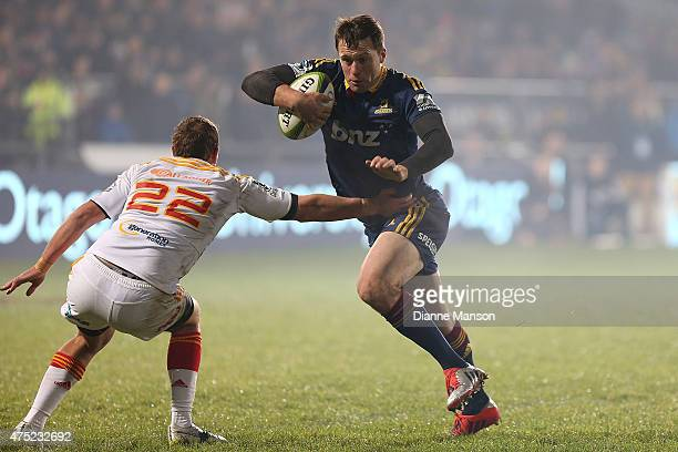 Ben Smith of the Highlanders looks to fend off Andrew Horrell of the Chiefs during the round 16 Super Rugby match between the Highlanders and the...