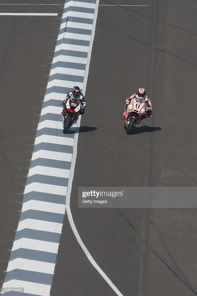 Ben Spies of USA and Ignite Pramac Racing Team and Blake Young of USA and Attack Performance Racing heads down a straight during the MotoGp Red Bull...