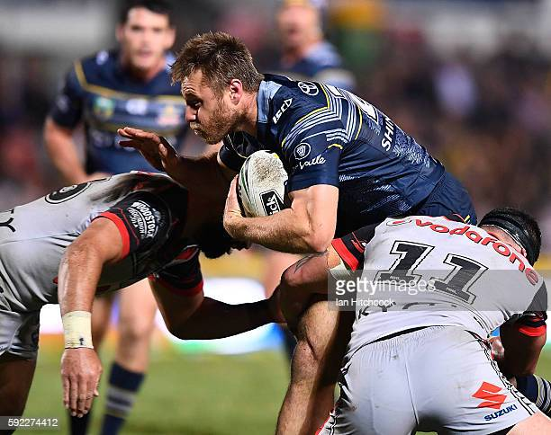 Ben Spina of the Cowboys is tackled by Bodene Thompson of the Warriors during the round 24 NRL match between the North Queensland Cowboys and the New...