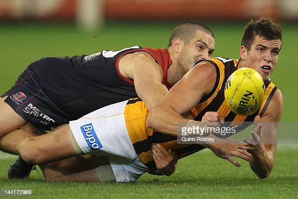 Ben Stratton of the Hawks handballs whilst being tackled by James Magner of the Demons during the round seven AFL match between the Melbourne Demons...