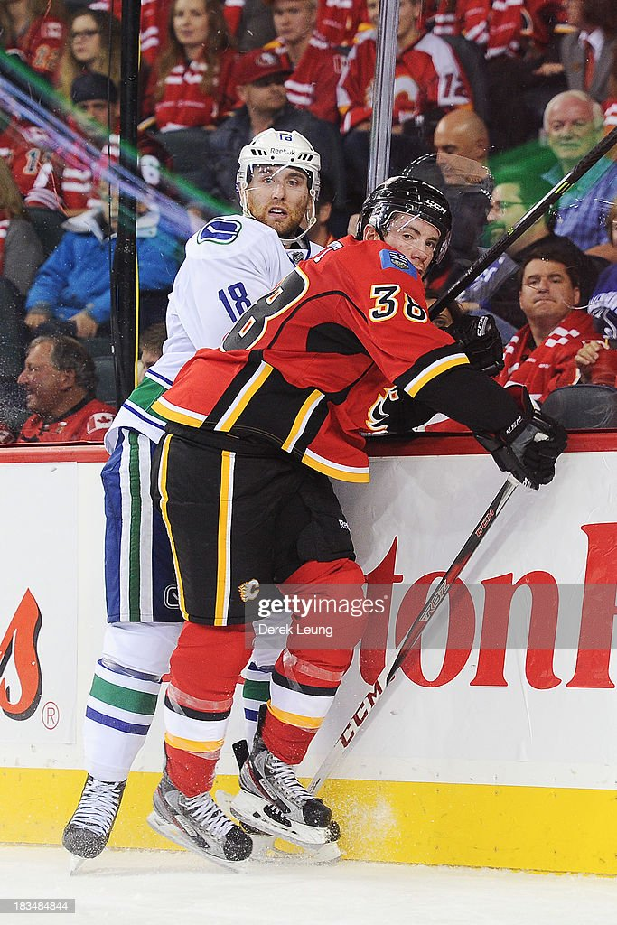 Ben Street #38 of the Calgary Flames flattens <a gi-track='captionPersonalityLinkClicked' href=/galleries/search?phrase=Ryan+Stanton&family=editorial&specificpeople=7184071 ng-click='$event.stopPropagation()'>Ryan Stanton</a> #18 of the Vancouver Canucks against the boards during the Flames' home opening NHL game at Scotiabank Saddledome on October 6, 2013 in Calgary, Alberta, Canada. The Vancouver Canucks won 5-4 in OT.