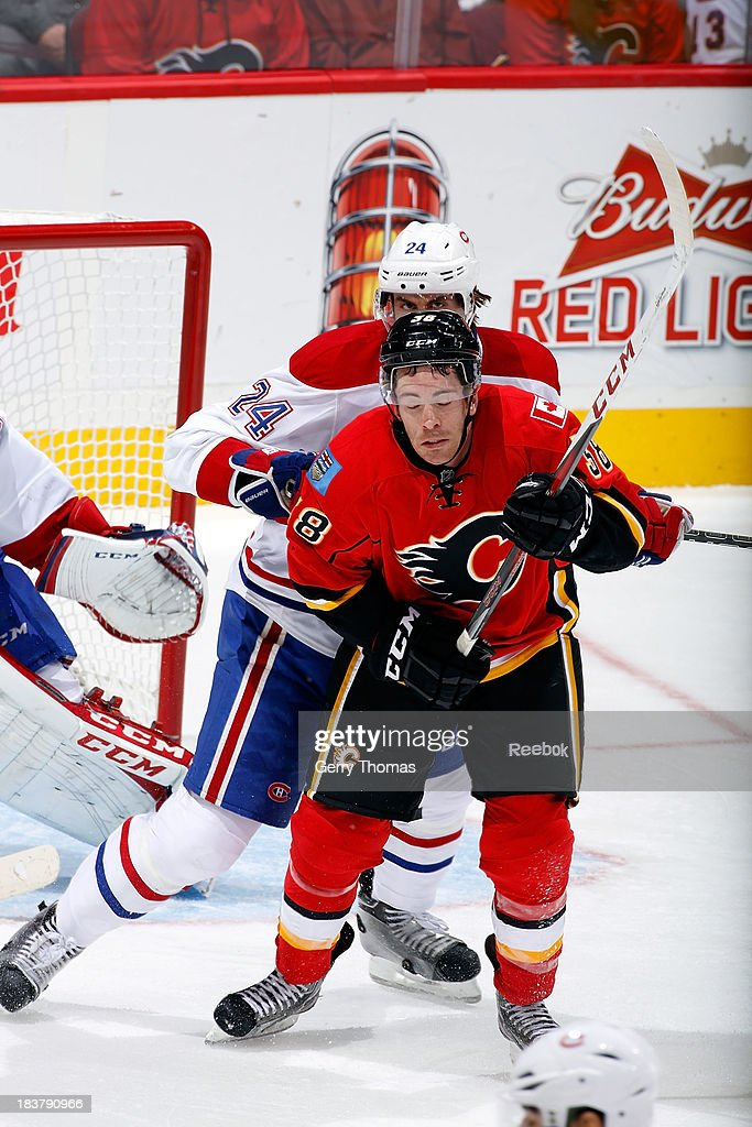 Ben Street #38 of the Calgary Flames is checked by Jarred Tinordi #24 of the Montreal Canadiens at Scotiabank Saddledome on October 9, 2013 in Calgary, Alberta, Canada.