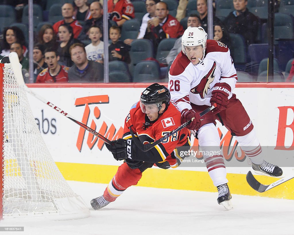 Ben Street #38 of the Calgary Flames is knocked off his feet by Michael Stone #26 of the Phoenix Coyotes as he attempts a wrap-around during a preseason NHL game at Scotiabank Saddledome on September 25, 2013 in Calgary, Alberta, Canada.