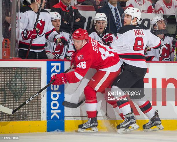Ben Street of the Detroit Red Wings battles along the boards with Taylor Hall of the New Jersey Devils during the final home game ever played at Joe...