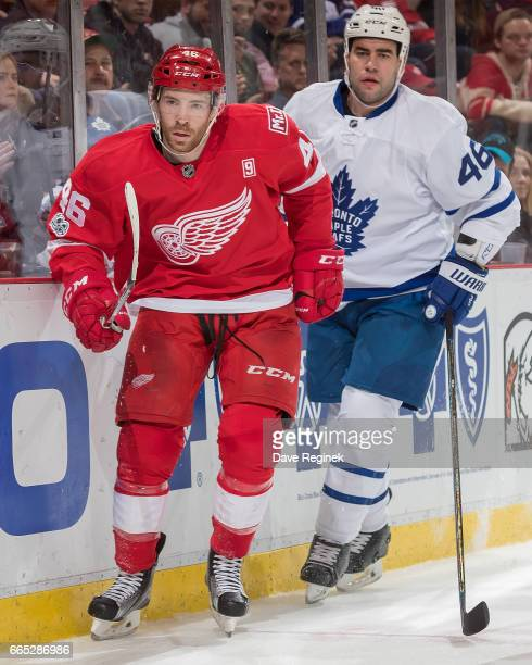 Ben Street of the Detroit Red Wings follows the play in front of Roman Polak of the Toronto Maple Leafs during an NHL game at Joe Louis Arena on...
