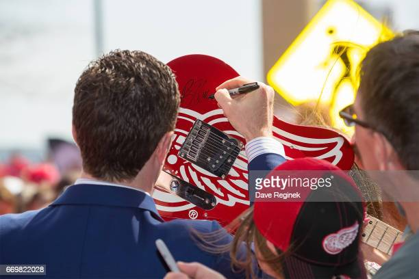 Ben Street of the Detroit Red Wings ''signs an electric guitar before the final home game ever played at Joe Louis Arena on April 9 2017 in Detroit...