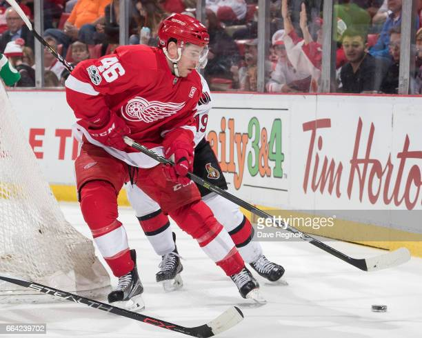 Ben Street of the Detroit Red Wings skates with the puck behind the net in front of Derick Brassard of the Ottawa Senators during an NHL game at Joe...
