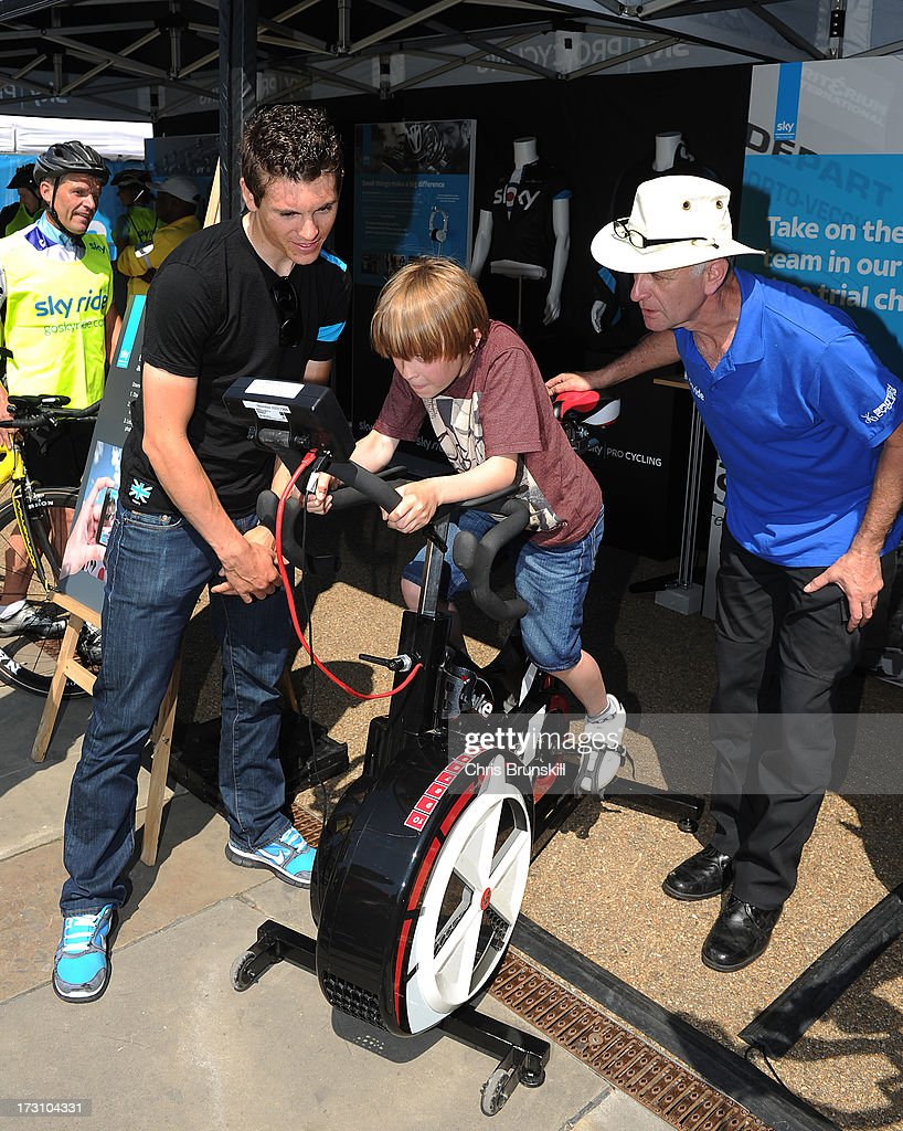 Ben Swift (L) assists a competitor during the Bike Watt Challenge at Sky Ride Leeds today - a free, fun, family cycling event from British Cycling and Sky held in partnership with Leeds City Council, offering people of all ages and abilities the chance to cycle around a traffic-free city on July 7, 2013 in Leeds, England. The ride celebrated the fact that the Tour de France will start in Leeds in 2014. Find a free organised bike ride near you and see how you can get involved at www.goskyride.com - there's something for everyone.