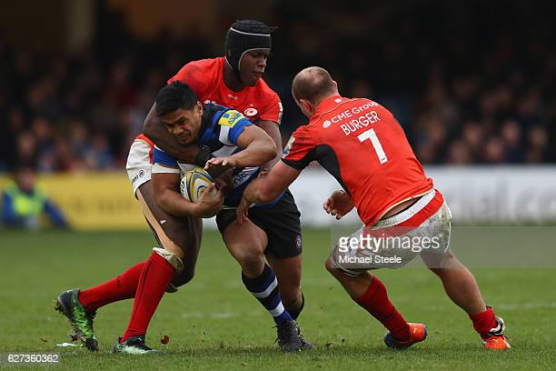 Ben Tapuai of Bath is held up by Maro Itoje and Schalk Burger of Saracens during the Aviva Premiership match between Bath Rugby and Saracens at the...