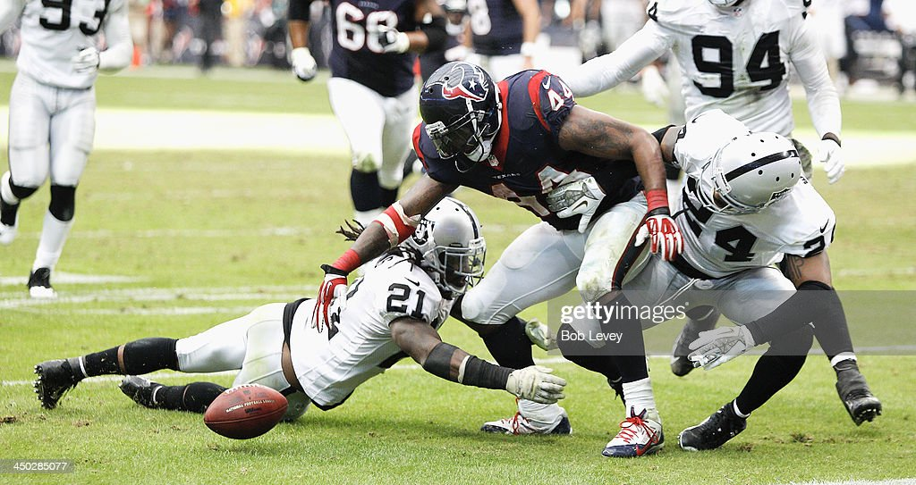 <a gi-track='captionPersonalityLinkClicked' href=/galleries/search?phrase=Ben+Tate&family=editorial&specificpeople=4091148 ng-click='$event.stopPropagation()'>Ben Tate</a> #44 of the Houston Texans fumbles the ball after taking a hard hit by <a gi-track='captionPersonalityLinkClicked' href=/galleries/search?phrase=Charles+Woodson&family=editorial&specificpeople=218111 ng-click='$event.stopPropagation()'>Charles Woodson</a> #24 of the Oakland Raiders and Mike Jenkins #21 at Reliant Stadium on November 17, 2013 in Houston, Texas. Oakland Raiders defeated the Houston Texans 28-23.