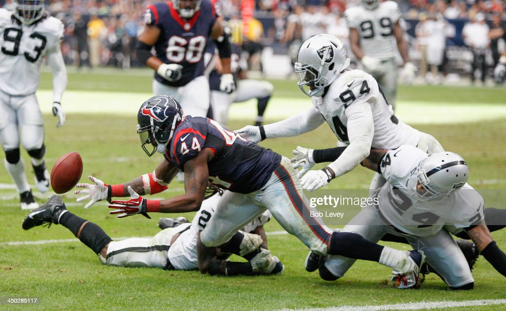 Ben Tate #44 of the Houston Texans recovers a fumble after taking a hard hit by Charles Woodson #24 of the Oakland Raiders and Mike Jenkins #21 at Reliant Stadium on November 17, 2013 in Houston, Texas. Oakland Raiders defeated the Houston Texans 28-23.