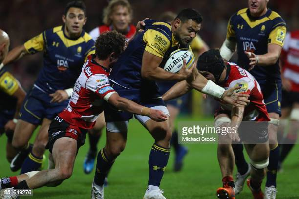 Ben Te'o of Worcester charges between Jacob Rowan and Jason Woodward of Gloucester during the Aviva Premiership match between Gloucester Rugby and...