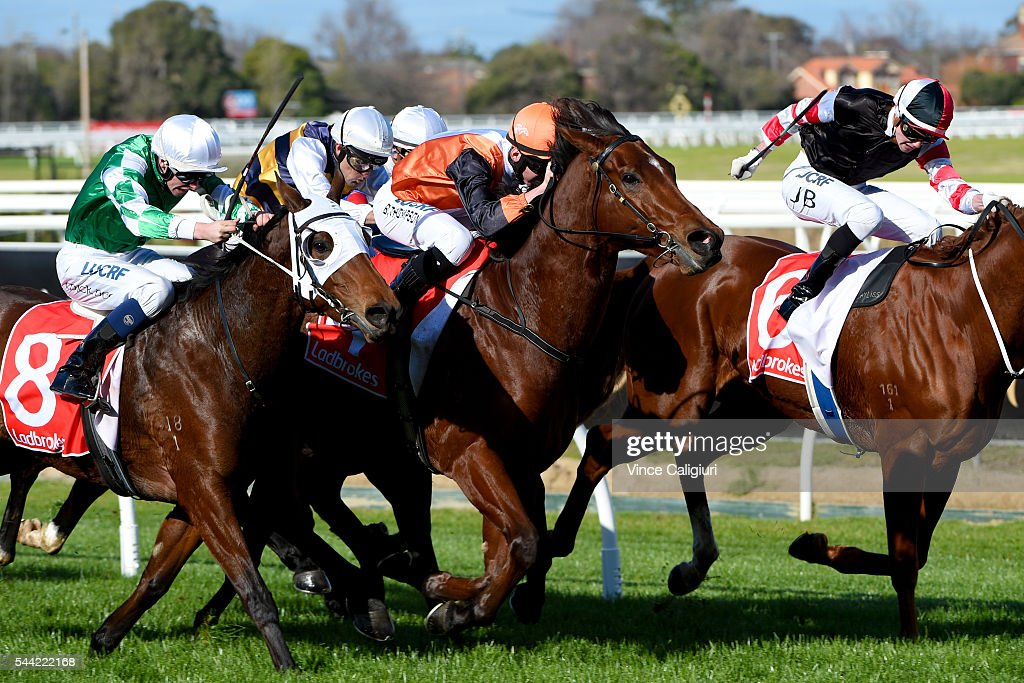 Ben Thompson riding Pin Your Hopes (orange) defeats Michael Dee riding Yulong Baby (8) in Race 3, during Melbourne Racing at Caulfield Racecourse on July 2, 2016 in Melbourne, Australia.