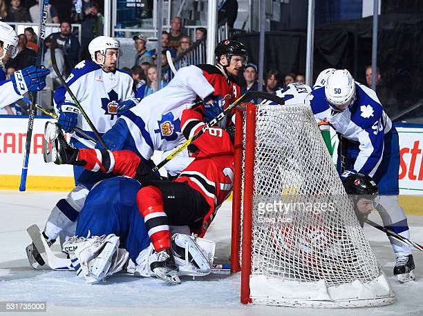 Ben Thomson of the Albany Devils is runs over Antoine Bibeau of the Toronto Marlies during AHL playoff game action on May 14 2016 at Ricoh Coliseum...
