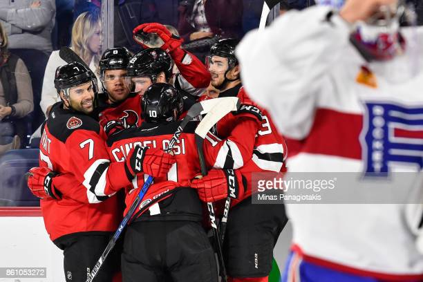 Ben Thomson of the Binghamton Devils celebrates his first period goal with teammates against the Laval Rocket during the AHL game at Place Bell on...
