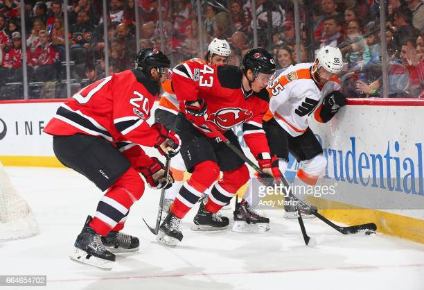 Ben Thomson of the New Jersey Devils battle for a loose puck with Nick Schultz of the Philadelphia Flyers during the game at Prudential Center on...