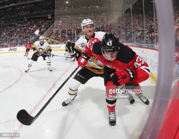 Ben Thomson of the New Jersey Devils is checked by Carter Rowney of the Pittsburgh Penguins during the second period at the Prudential Center on...