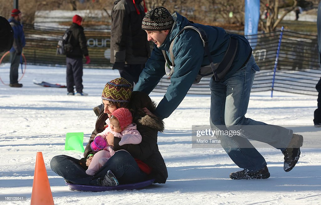 Ben Tolchin pushes Dorothy Tolchin as she holds daughter Natalie at the Winter Jam in Central Park on January 26, 2013 in New York City. The annual festival brings skiing, snowboarding and snowshoeing to New Yorkers with free equipment.