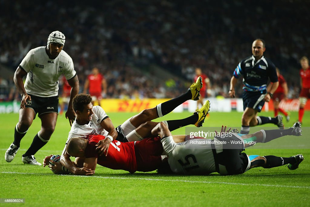 Ben Volavola (L) and Metuisela Talebula of Fiji (R) fail to stop Mike Brown of England scoring their third try during the 2015 Rugby World Cup Pool A match between England and Fiji at Twickenham Stadium on September 18, 2015 in London, United Kingdom.