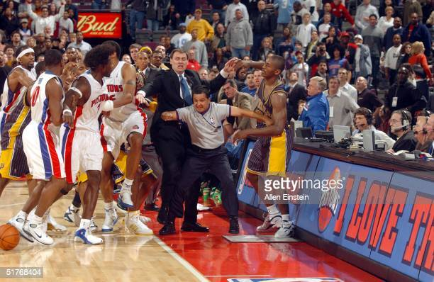 Ben Wallace of the Detroit Pistons and teammates are kept apart from Ron Artest of the Indiana Pacers by Pacers head coach Rick Carlisle and official...