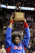 Ben Wallace of the Detroit Pistons holds up his NBA Defensive Player of the Year Award given to him prior to the start of Game five of the Eastern...