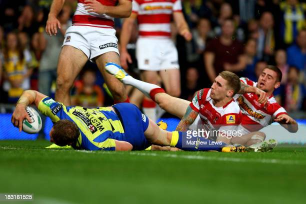 Ben Westwood of Warrington powers through the tackle from Sam Tomkins and Michael McIlorum of Wigan to score his team's third try during the Super...