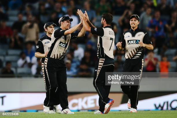 Ben Wheeler of New Zealand celebrates with teammates Colin de Grandhomme and Tim Southee after taking a catch to dismiss AB de Villiers of South...