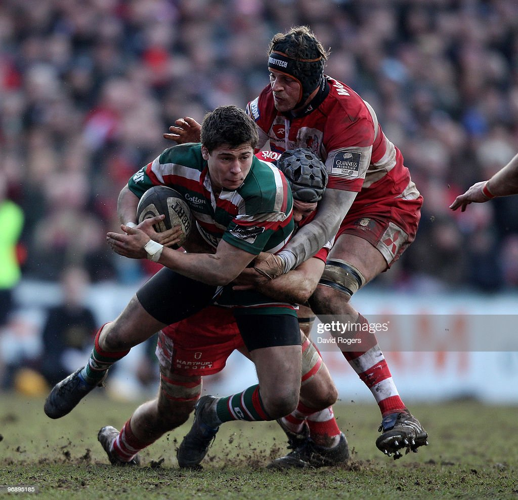 Ben Youngs of Leicester is held by Andy Hazell and Alex Brown during the Guinness Premiership match between Leicester Tigers and Gloucester at...