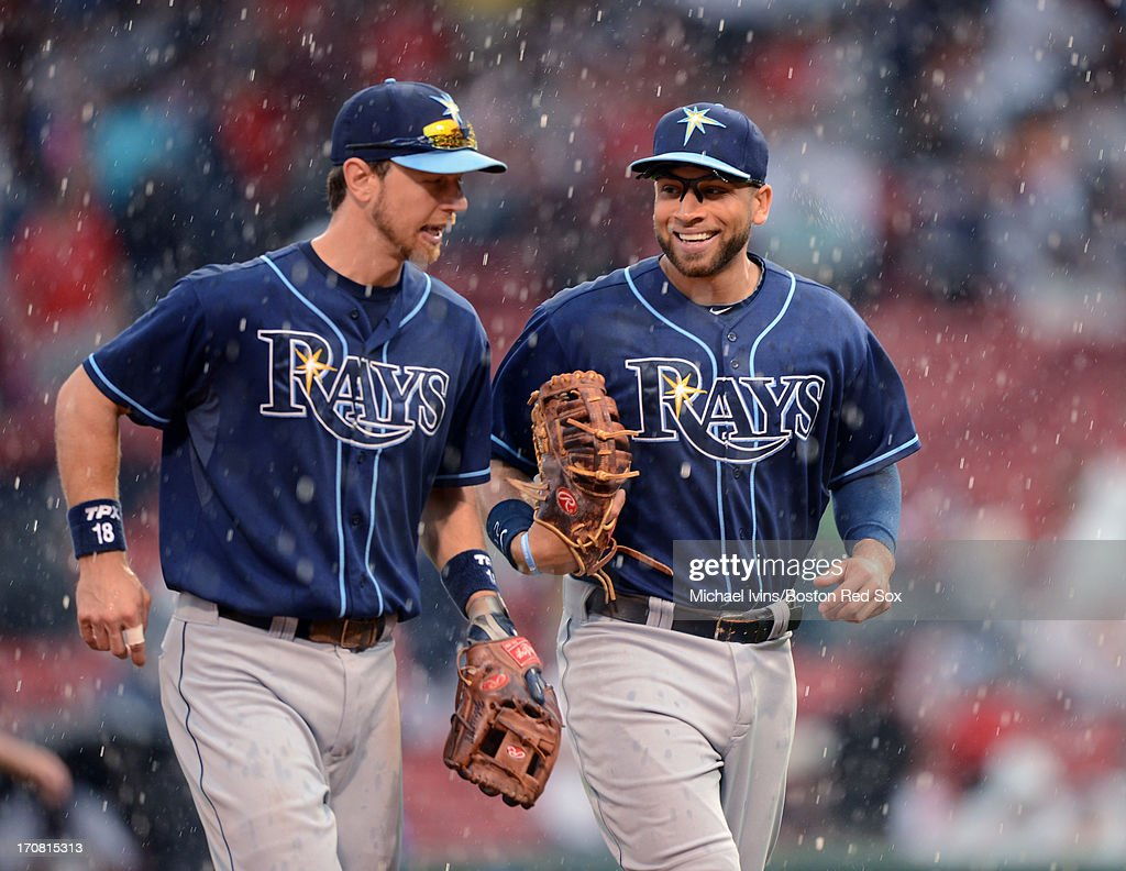 Ben Zobrist #18 and James Loney #21 of the Tampa Bay Rays run off the field during a rain delay against the Boston Red sox in the fifth inning on June 18, 2013 at Fenway Park in Boston, Massachusetts.