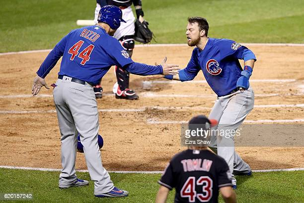 Ben Zobrist of the Chicago Cubs celebrates with teammate Anthony Rizzo after crashing into Roberto Perez of the Cleveland Indians to score a run in...