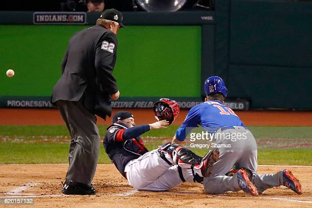 Ben Zobrist of the Chicago Cubs crashes into Roberto Perez of the Cleveland Indians to score a run in the first inning on a double hit by Ben Zobrist...