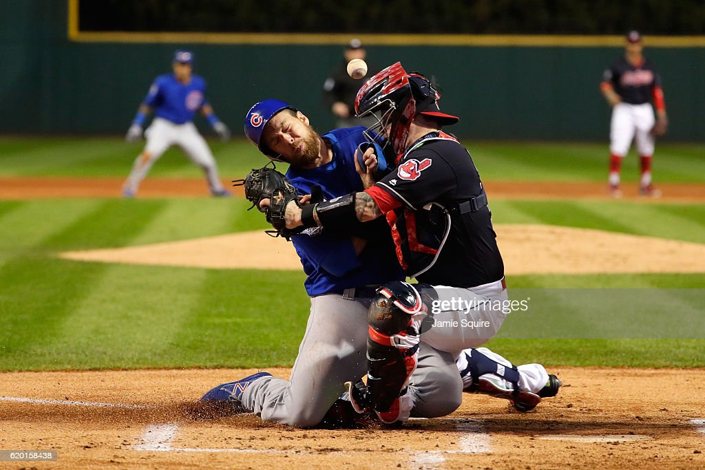 Ben Zobrist #18 of the Chicago Cubs crashes into Roberto Perez #55 of the Cleveland Indians to score a run in the first inning on a double hit by Addison Russell #27 (not pictured) in Game Six of the 2016 World Series at Progressive Field on November 1, 2016 in Cleveland, Ohio.