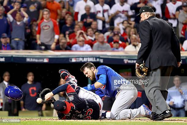 Ben Zobrist of the Chicago Cubs crashes into Roberto Perez of the Cleveland Indians to score a run in the first inning on a double hit by Addison...