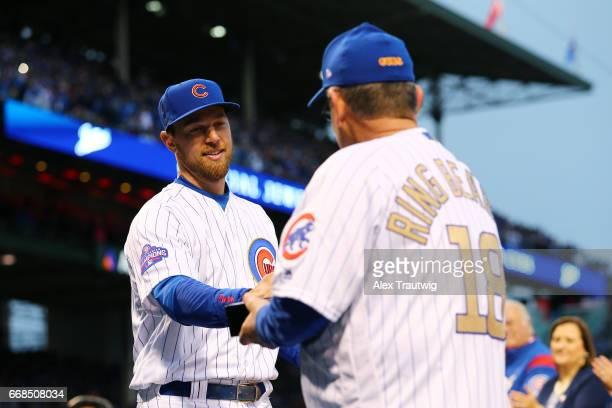 Ben Zobrist of the Chicago Cubs receives his ring from a fan during the World Series ring ceremony ahead of the game between the Los Angeles Dodgers...