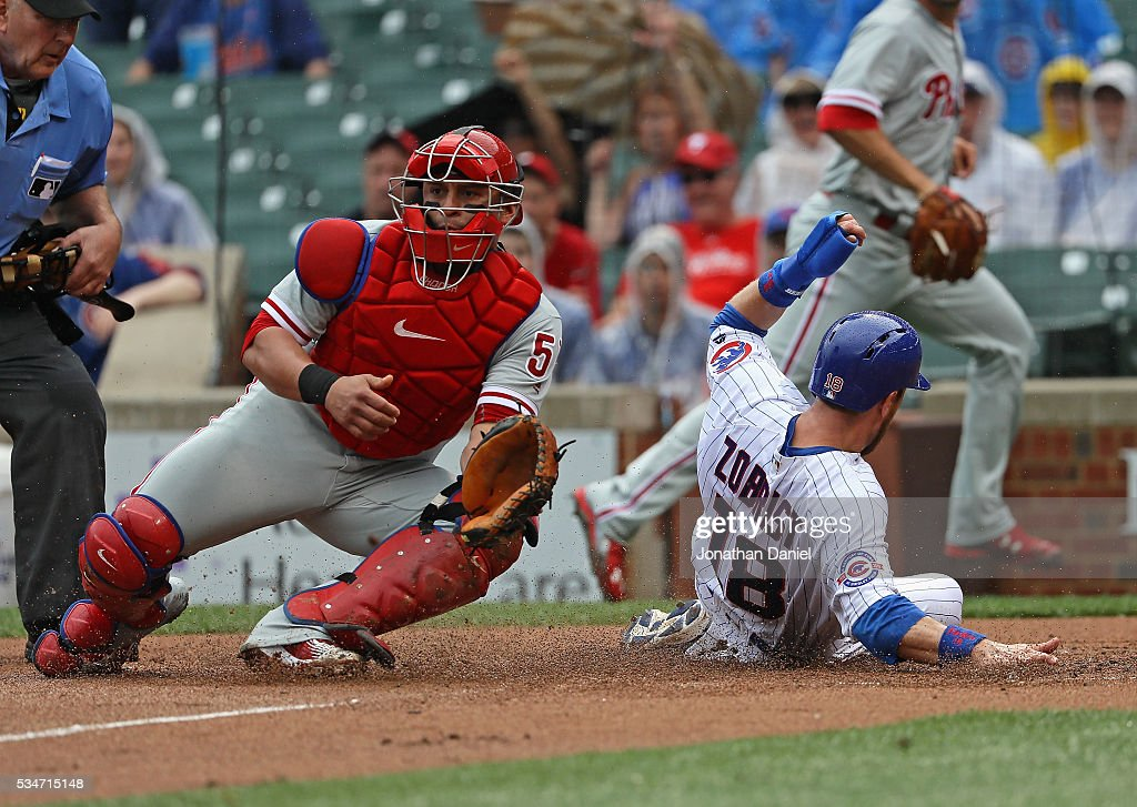 Ben Zobrist of the Chicago Cubs slides in to score a run in the 1st inning as Carlos Ruiz of the Philadelphia Phillies awaits the throw at Wrigley...