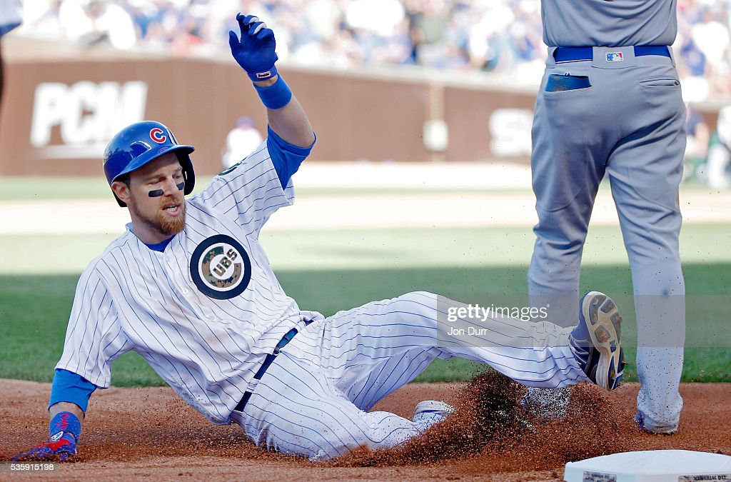 Ben Zobrist #18 of the Chicago Cubs slides into third base after hitting a triple against the Los Angeles Dodgers during the fifth inning at Wrigley Field on May 30, 2016 in Chicago, Illinois.