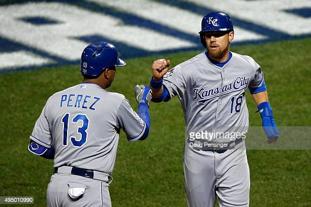 Ben Zobrist of the Kansas City Royals celebrates after scoring in the first inning against the New York Mets with teammate Salvador Perez during Game...