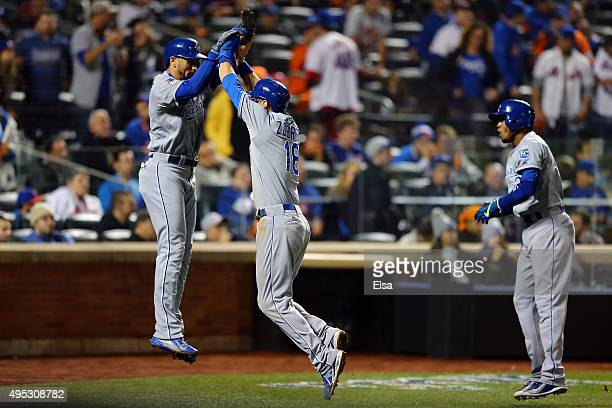 Ben Zobrist of the Kansas City Royals celebrates with Christian Colon and Alcides Escobar after scoring off of a three run RBI double hit by Lorenzo...