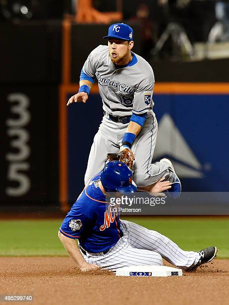 Ben Zobrist of the Kansas City Royals jumps after throwing to first as Daniel Murphy of the New York Mets slides into second during Game 5 of the...