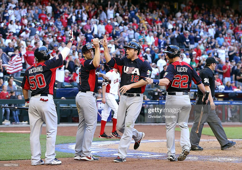 Ben Zobrist #12 of USA high fives <a gi-track='captionPersonalityLinkClicked' href=/galleries/search?phrase=David+Wright+-+Baseball+Player&family=editorial&specificpeople=209172 ng-click='$event.stopPropagation()'>David Wright</a> #5, <a gi-track='captionPersonalityLinkClicked' href=/galleries/search?phrase=Shane+Victorino&family=editorial&specificpeople=576251 ng-click='$event.stopPropagation()'>Shane Victorino</a> #50 and <a gi-track='captionPersonalityLinkClicked' href=/galleries/search?phrase=Jonathan+Lucroy&family=editorial&specificpeople=5732413 ng-click='$event.stopPropagation()'>Jonathan Lucroy</a> #22 after scoring against Canada during the ninth inning of the World Baseball Classic First Round Group D game at Chase Field on March 10, 2013 in Phoenix, Arizona.