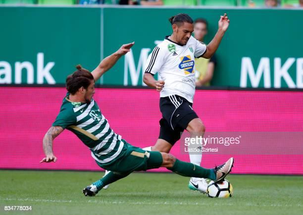 Bence Batik of Ferencvarosi TC slide tackles David Williams of Swietelsky Haladas during the Hungarian OTP Bank Liga match between Ferencvarosi TC...